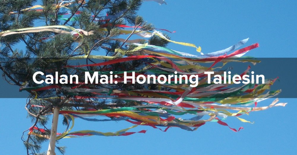 "Brightly colored ribbons stream from a small pine tree against a clear blue sky. The words ""Calan Mai: Honoring Taliesin"" are superimposed."