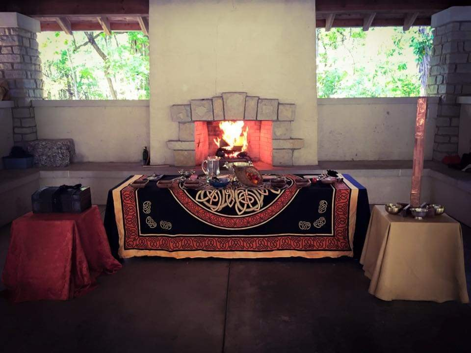 A altar covered in an orange and black tapestry sits before a merry fire