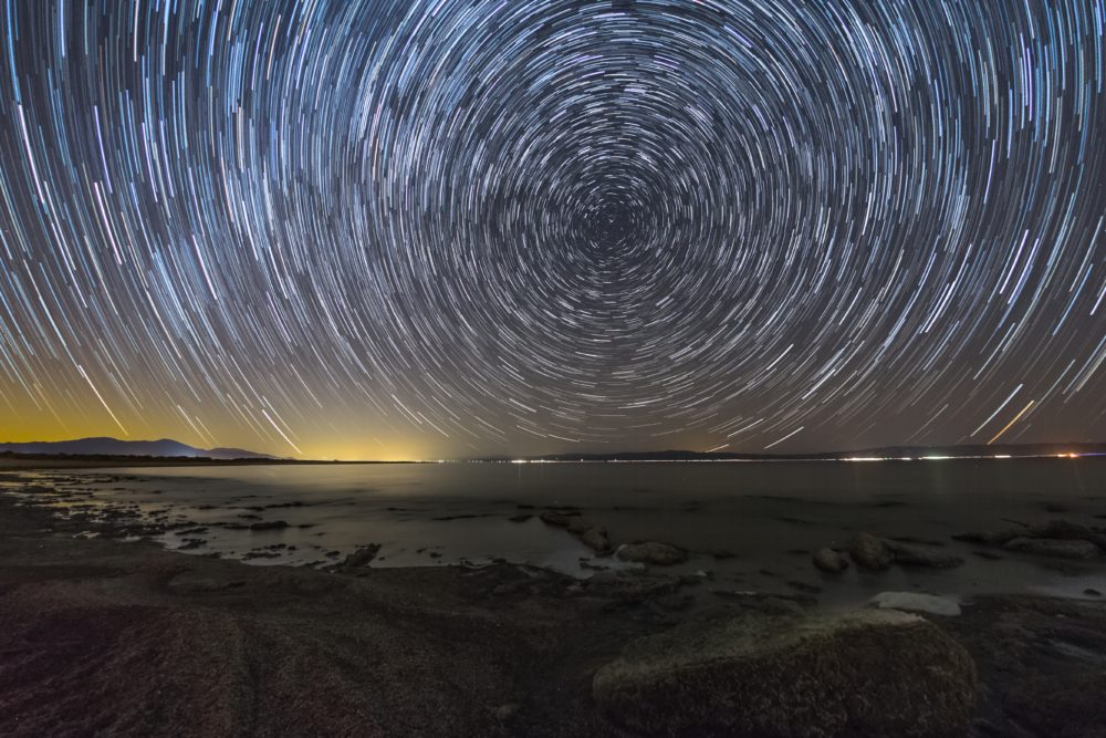 In a long-exposure shot, the stars make circling, concentric trails in the night sky.